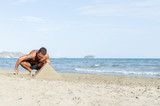 Man making pyramind from sand - 175657200
