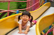 滑り台で元気に遊ぶ女の子(夏)