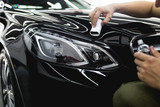 Worker cleaning car - car detailing (or valeting) concept. Selective focus.