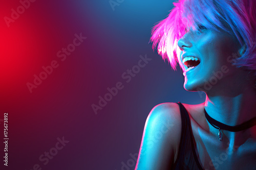 Beauty model girl in colorful bright lights with trendy makeup and haircut Poster