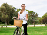 Beautiful young blonde woman with bike in park - 175678097