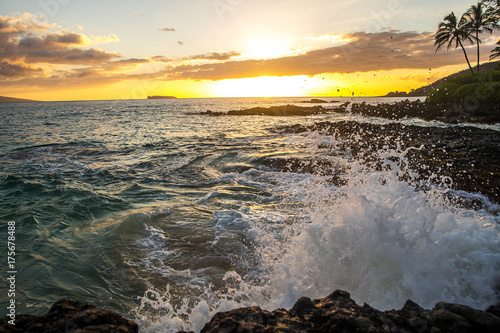 Fotobehang Strand Ocean waves crashing on rocks at a tropical island beach