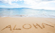 The word Aloha written in sand at the beach