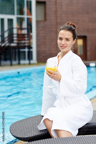 Calm young woman with refreshing drink sitting by swimming pool at spa resort