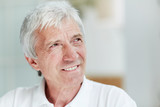 Headshot of handsome senior man looking away with warm toothy smile, blurred background - 175688886