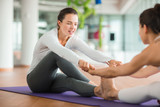 Pretty sporty women doing stretching exercise while sitting on yoga mats and holding hands, interior of spacious health club on background - 175689654
