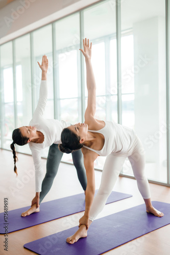 Fotobehang Fitness Fit young women warming up muscles before intensive workout at spacious fitness club with panoramic windows, they doing side bend