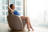 Relaxed young woman resting on comfortable armchair with eyes closed hands behind head at home, happy lady relaxing in cozy designer chair near full-length window with city view, time for yourself - 175700437