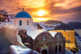 Amazing sunrise at Oia town on Santorini island, Greece. Traditional and famous houses and churches with blue domes over the Caldera, Aegean sea - 175701030