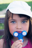 Little caucasian girl in white cap holds a spinner by the chin and smiles outdoor. - 175708039