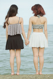 Portrait  of lesbian lover holding hands together. Two woman stand back at sea in Thailand and touch hand together, This image for lesbian concept  vintage style. - 175709803