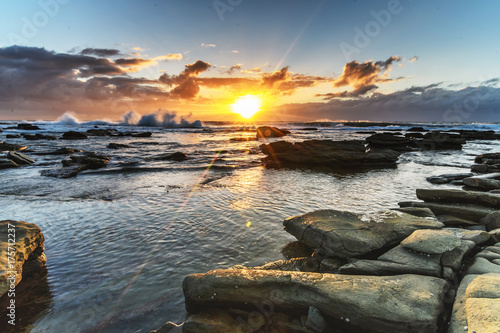 Deurstickers Ochtendgloren Cloudy and Rocky Sunrise Seascape