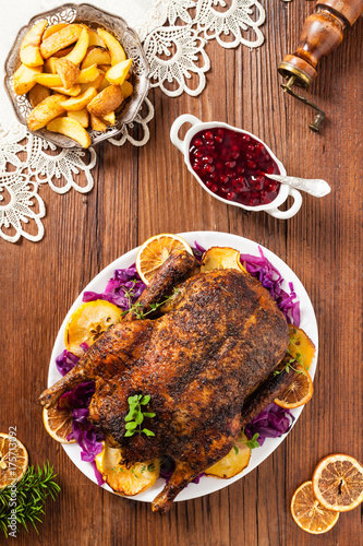 Baked whole duck, served with apples, red cabbage, oranges and roasted fritters. - 175713092