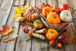 Autumn still life with pumpkins, corncobs, fruits and leaves
