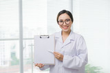 Asian woman doctor standing with folder at hospital - 175725237