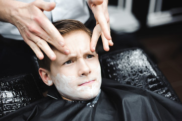 Funny boy in a black salon cape in the barbershop. Barber applies shaving foam with the help of the shaving brush on his face.