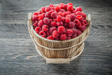 Raspberries in bucket on wooden board - 175734498