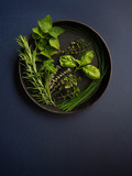 Various fresh green herbs in black pan on blue background. Mint, parsley, oregano, basil, thyme, chive, rosemary. - 175747669
