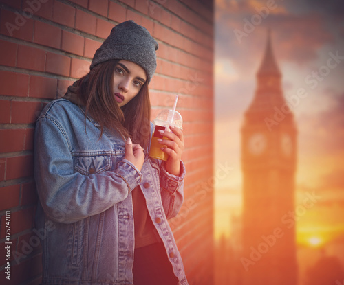 In de dag Londen girl in a jeans jacket drinks juice on a Big Ben
