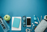 Modern Work space for healthy person: pencils, water, apple, phone, glasses, headphones on a blue background. Top view, flat lay - 175757627