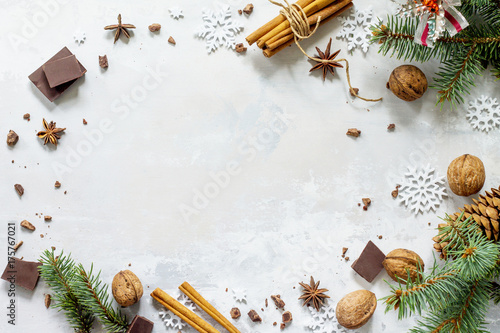 obraz lub plakat Ingredients for Christmas baking - chocolate, cinnamon, anise and nuts on a stone or slate background. Seasonal, food background.
