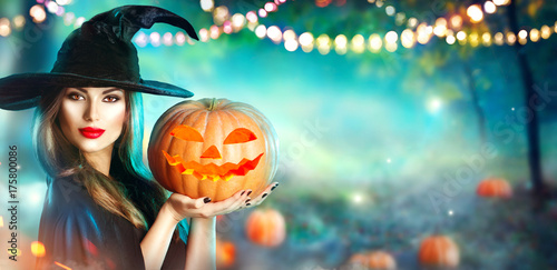 Halloween witch with a carved pumpkin and magic lights in a dark forest - 175800086