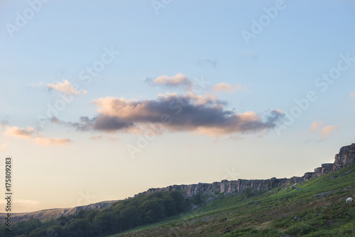 Stunning landscape image of Stanage Edge during Summer sunset in Peak District Egland