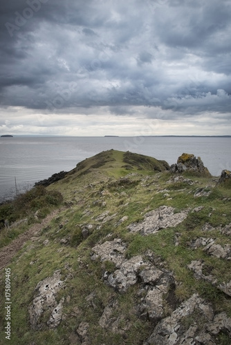 Foto op Aluminium Bleke violet Looking out to sea at stormy dramatic sky over landscape