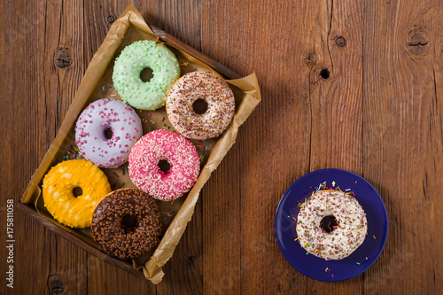 Colorful donuts on a wooden background. Poster