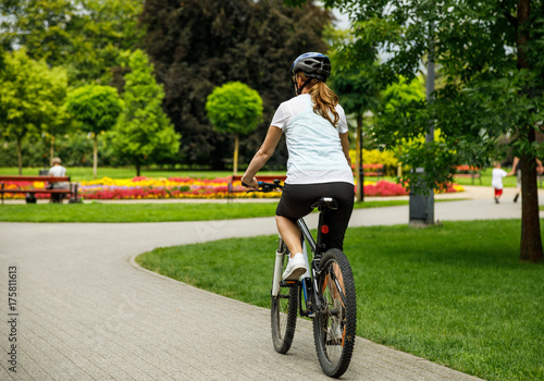 Healthy lifestyle - woman riding bicycle in city park