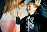 Waist-up portrait of laughing little boy wearing skeleton costume enjoying Halloween home party, blurred background - 175824076