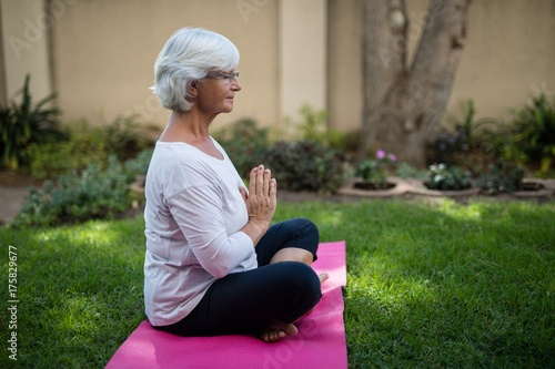 Side view of senior woman meditating in prayer position