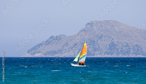 Deurstickers Groen blauw A small sailing boat in Alcudia bay near Can Picafort town, Majorca