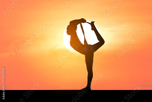 Sticker Silhouette of a beautiful Yoga woman with sun background