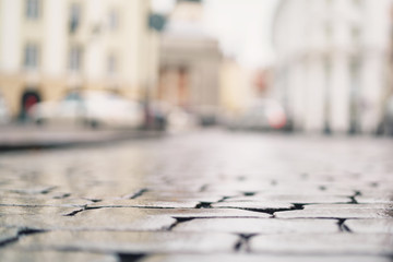 low angle shot of wet old pavement in Tallinn with shallow focus