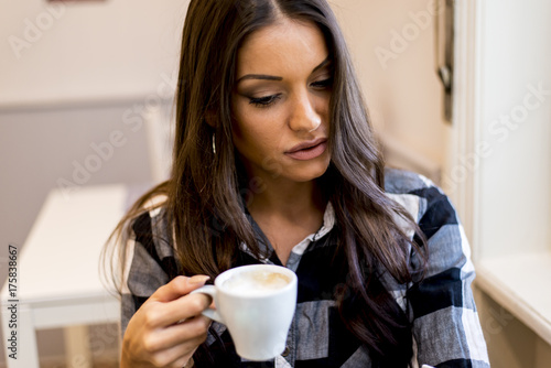 Pretty young woman drinking coffee Im cafe