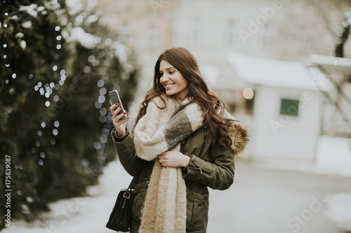 Young woman using phone in park at  cold winter day