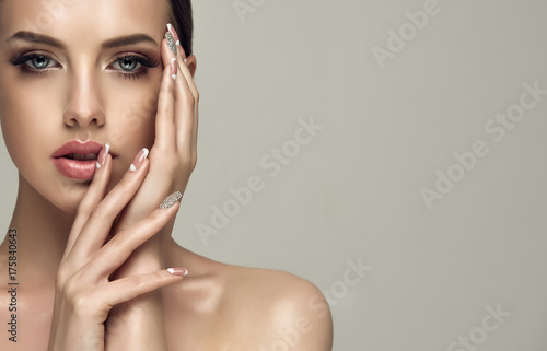 Fotobehang Manicure Beautiful model girl with a beige French manicure nail design with rhinestones . Fashion makeup and care for hands and nails and cosmetics