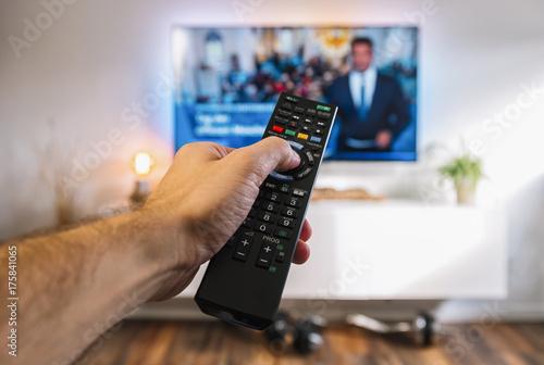 canvas print picture Fernsehen mit Fernbedienung in der Hand