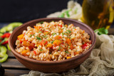 Vegetarian crumbly pearl barley porridge with vegetables  in a dark background - 175843087
