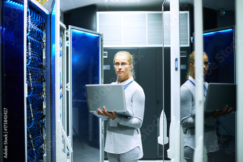 Portrait of young woman working with supercomputer standing in center of server room holding laptop, copy space