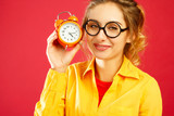 Portrait of a beautiful sleepy woman holding clock in hands over red background