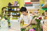 Happy asian male florist using laptop at counter in flower shop - 175850095