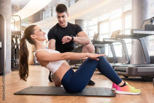 Frau beim Training im Gym mit Fitness Lehrer macht Core Übungen