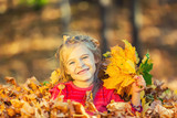 Happy little girl plays with autumn leaves in the park - 175854428