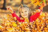 Happy little girl plays with autumn leaves in the park - 175854432