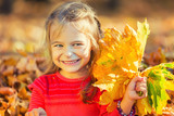 Happy little girl with autumn leaves in the park