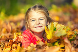 Happy little girl plays with autumn leaves in the park - 175854456