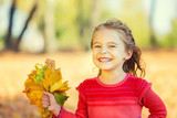 Happy little girl with autumn leaves in the park - 175854461