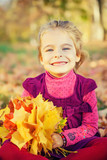 Happy little girl with autumn leaves in the park - 175854485
